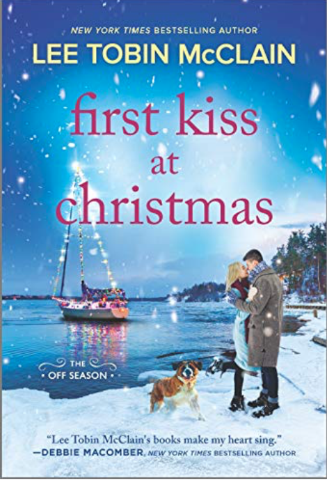 m/f couple embracing while st bernard dog romps beside them. Background has a sailboat with Christmas lights